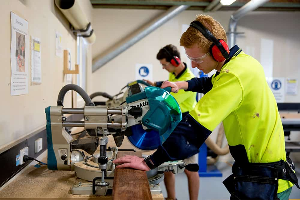 Construction student using machinery to cut a plank of wood